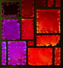 Ausschnitt aus einem geometrischen Buntglasfenster in Rot- und Violetttönen