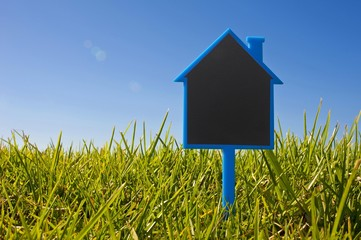 Blank sign shaped like a house in the grass, symbolic image for house purchase