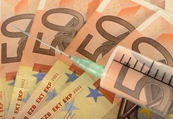 Syringe on banknotes, symbolic image for cash injection