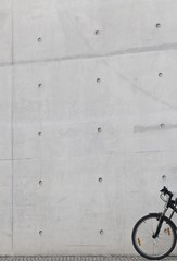 Bicycle leaning against a bare concrete wall, Berlin, Germany, Europe