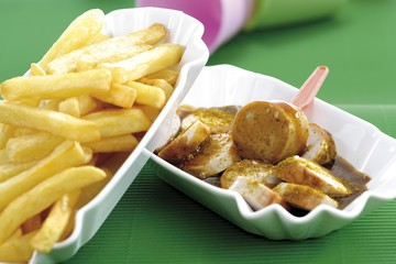 Chips and curry sausage on a small plate