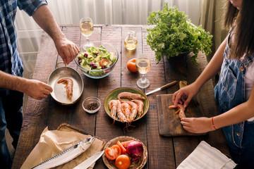 Couple cooking together shrimp dinner and vegetables salad