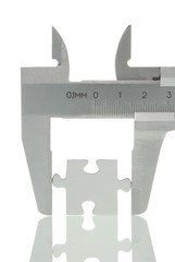 Calipers with a puzzle piece, symbolic image for analysis of a piece