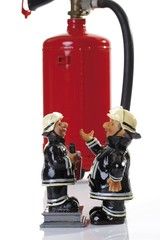 Miniature figures of fire fighters in front of a fire extinguisher