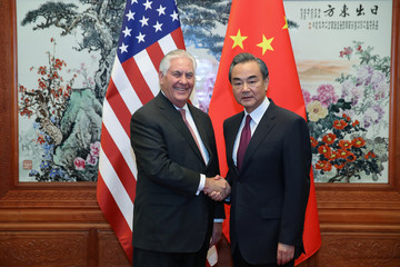 U.S. Secretary of State Rex Tillerson (L) shakes hands with Chinese Foreign Minister Wang Yi (R) before their meeting at the Great Hall of the People in Beijing