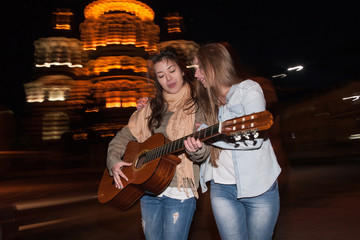 Nightlife girlfriends, girls with a guitar. Young people walk at night against the blurred city lights