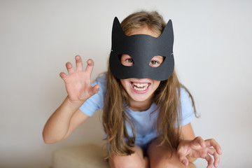 The girl plays in a self-made mask of black cat