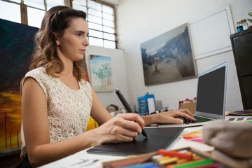 Woman using graphic tablet and laptop in drawing class