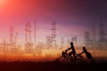 Silhouette young asian ride bicycle on energy saving garden and oil refinery plant at twilight.