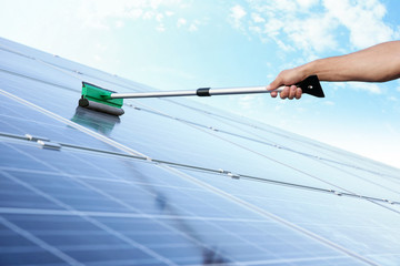 Hand of worker washing solar panels after installation outdoors