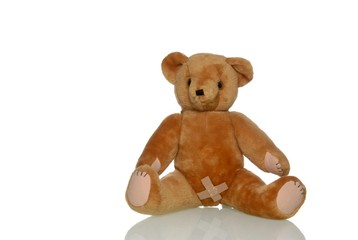 Sad teddy bear with a plaster in the genital area, symbolic image for abuse