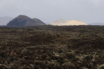 Field with clumps of lava in front of Caldera de los Arrables in the uninhabited mountain region Malpais Grande, Fuerteventura, Canary islands, Spain, Europe