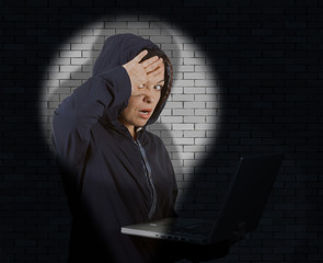 Criminal Woman Hacker Wearing Hood On Using a Laptop Catched with Flashlight