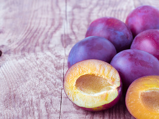 Large red sweet plum and cut off half on a wooden background with empty space