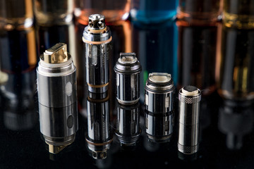 Electronic cigarette steel coils in a row with e-juice bottles in the background