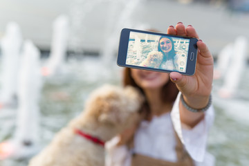 Say cheese. Woman taking selfie with her dog outdoor