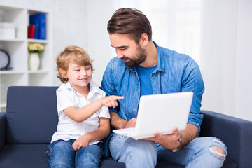 young father and son sitting on sofa with laptop