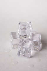 Ice cubes with water drops on the white marble background