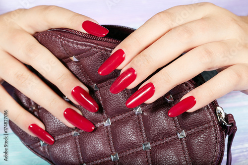 Hands With Long Artificial Manicured Nails Colored Red Nail Polish Holding A Handbag