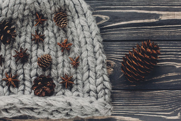 christmas anise and pine cones on warm  woolen hat on rustic background top view, space for text. hipster stylish wear. xmas seasonal greetings card flat lay. winter holiday mood