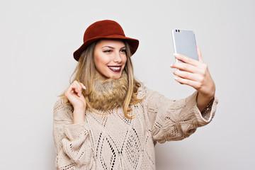 Modern autumn fashion woman taking a selfie on smart phone
