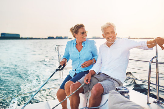 Smiling mature couple enjoying a sunny day sailing together