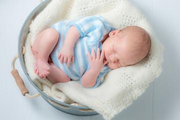Cute newborn infant sleeping in small bath