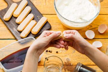 Picture of tiramisu cooking, human hands with savoyardi cookies