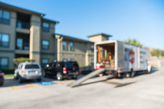 Blurred image of parked truck with open door, loading ramp waiting to transport for apartment moving. Relocate home, condominiums, housing, re-arranging furniture service/work concept background.