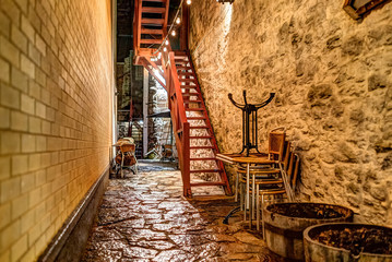 Narrow alley with cobblestone and private entrance with stairs to stone apartment at night