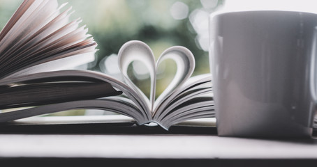 A book open in heart shape and a cup of coffee