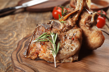 Wall Mural - Wooden board with tasty meat on table, closeup