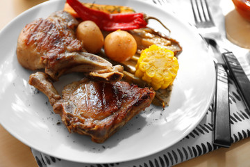 Plate with grilled meat on table
