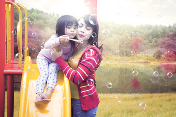Family blowing soap bubble on slide
