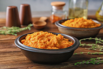 Bowl with mashed sweet potato on wooden table
