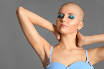 Beautiful bald woman in blue dress against grey background