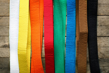 Colorful karate belts on wooden background