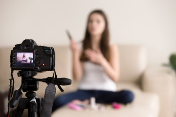 Young female videoblogger sitting on sofa, records commercial beauty product review for personal video blog. Vlogger uses contemporary photo camera to create footage for popular internet vlog at home.