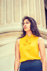 East Indian American Business Woman in New York. Wearing sleeveless orange shirt, a college female student standing by column outside office, confidently looking forward. Instagram filtered effect.