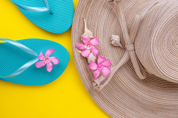 Women Straw Hat with Bow Pink Tropical Flowers Blue Slippers Sea Shells on Yellow Background Beach Vacation Seaside Traveling Fashion Flat Lay Copyspace