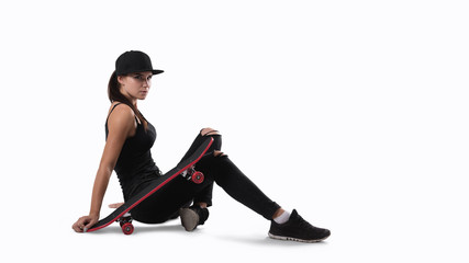 Young beautiful brunette woman with skate posing in studio