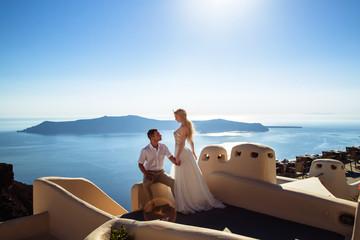 beautiful bride and groom in their summer wedding day on greek island Santorini