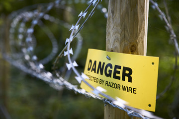 Yellow Danger Sign with Razor Wire