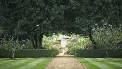 Pathway to an ornate wrought iron gate through landscaped gardens