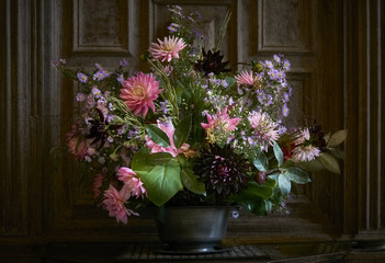 Autumn flower arrangement in a rustic pewter vase indoors in front of oak panelling