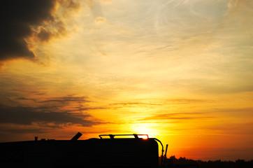 Silhouette tramonto con camper e montagne