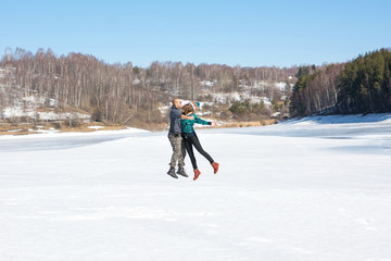 Happy friends jumping on a frozen lake