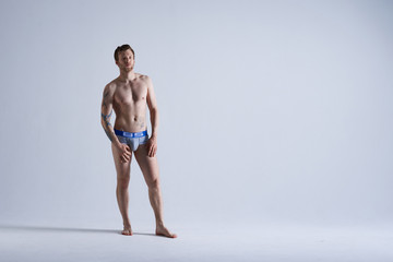 People, style and fashion concept. Full length isolated portrait of handsome muscular athletic adult European male model with beard posing in studio for underwear advertisement or commercial