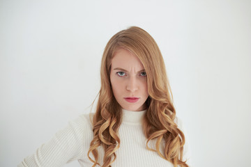 Picture of serious angry adult woman with blue eyes and curly hair frowning feeling furious, avenging herself on husband for cheating on her. Negative human emotions, reaction, feelings and attitude