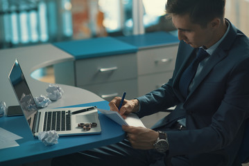 Employee checks  document/ Manager in a business suit reads the contract document and signs it with a pen on the office desk. On the table is a laptop, spinner, crumpled paper